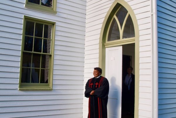 Pastor standing at the entrance to a church to welcome people in