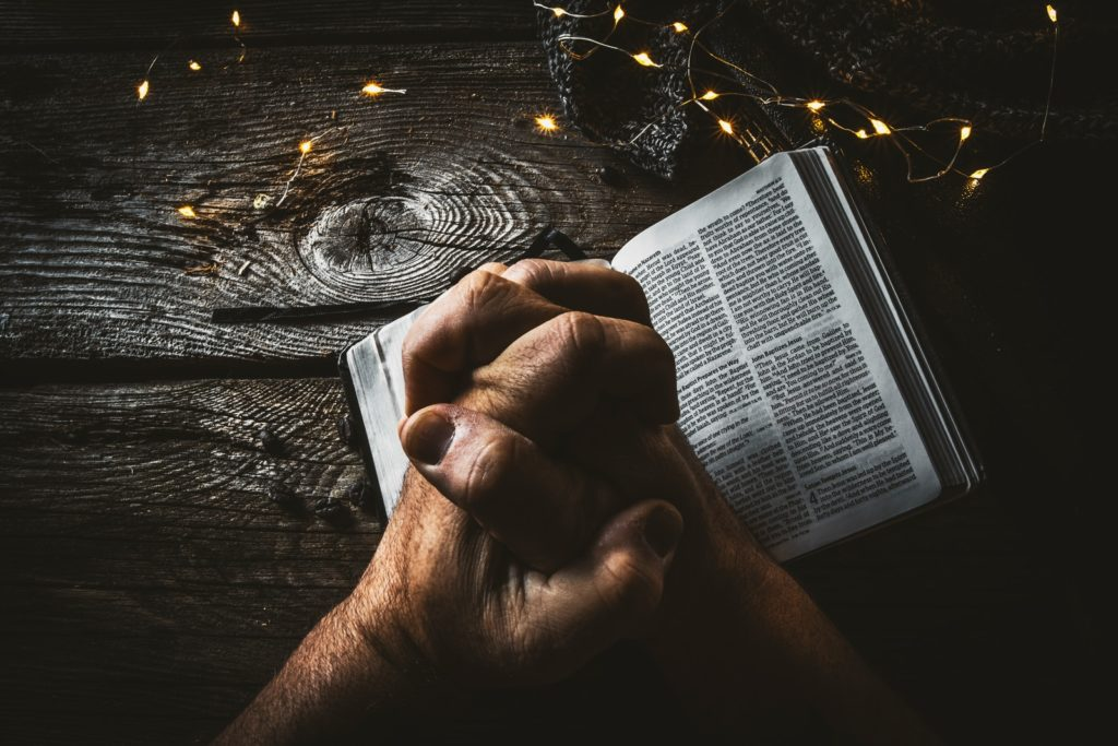 hands folded in prayer resting on an open Bible