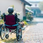 woman sitting on wheelchair facing away from the camera in a residential area.