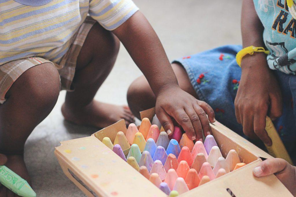 two kids sharing a box of sidewalk chalk