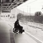 Person in wheelchair at train station on the edge of the platform