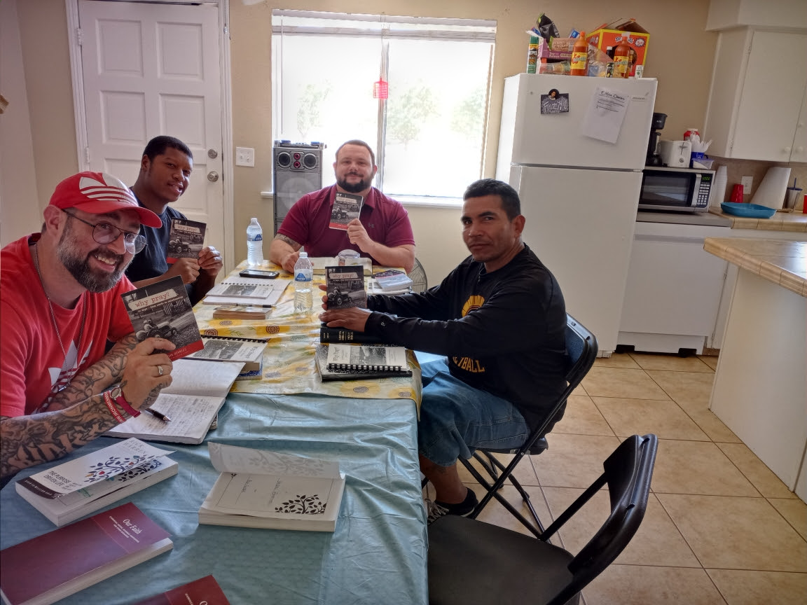 Men with open Bible study books at a kitchen table.