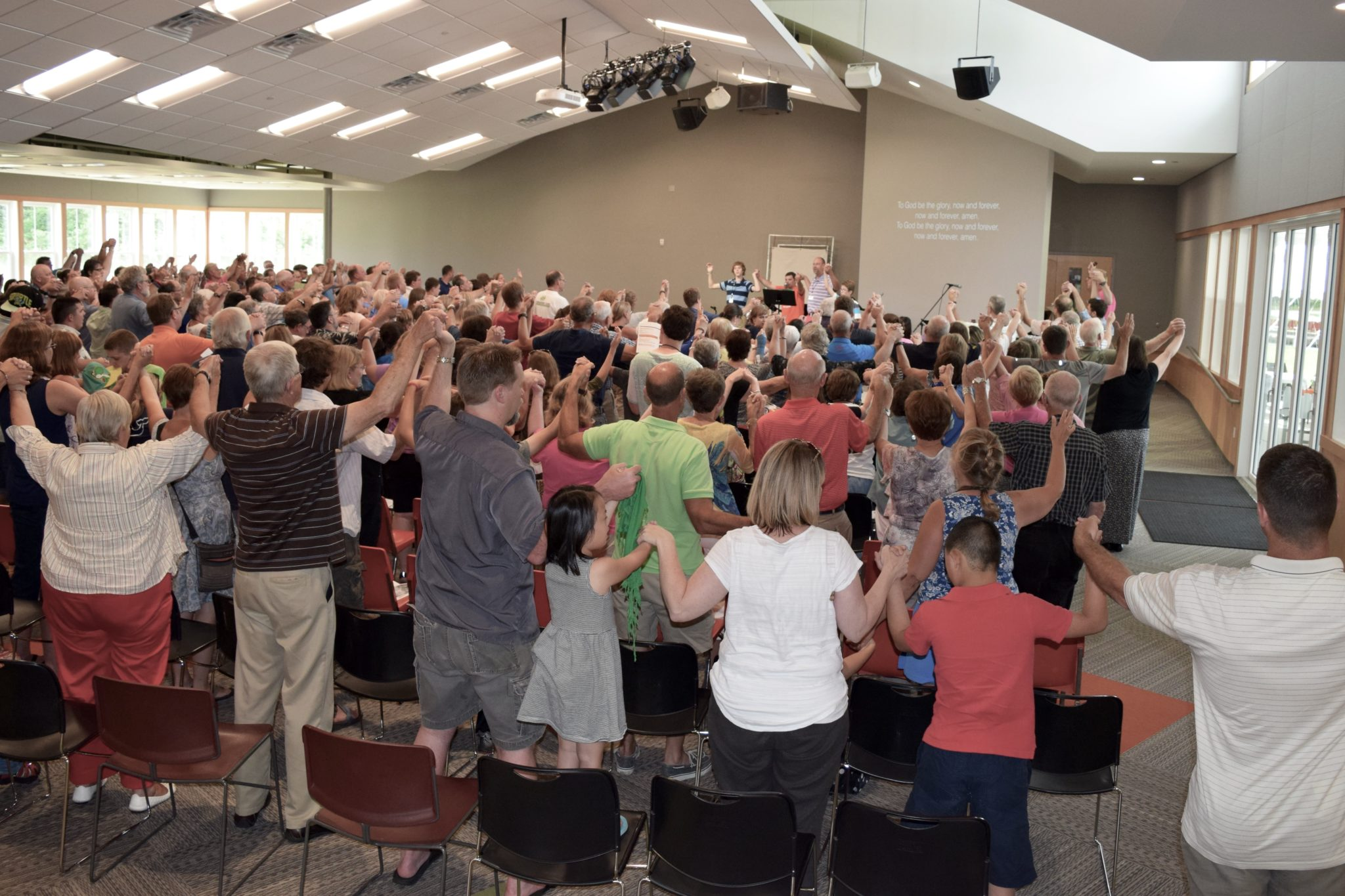 People join hands during worship in a church sanctuary.