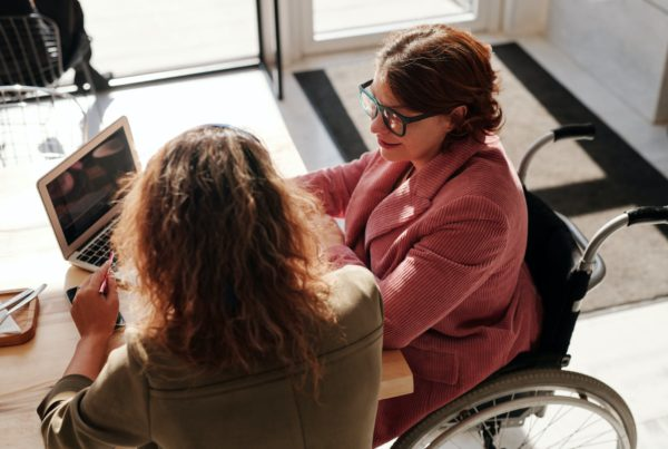 Two women sit with a laptop at a local coffee shop. One is in a wheelchair.