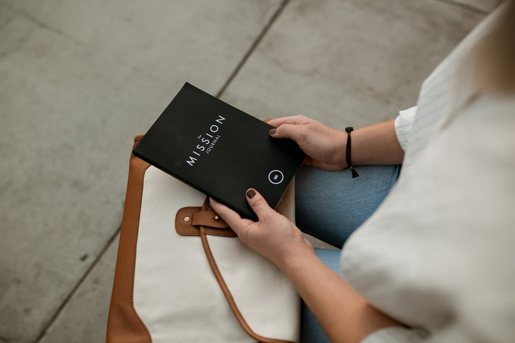 A young woman in a white sweater sits with a mission journal on her lap.