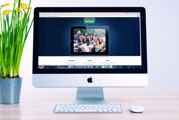 Apple computer shows photo of happy people on a website home page