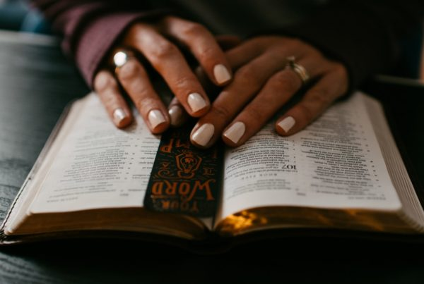 woman's hands are loosely folded over an open Bible with a bookmark