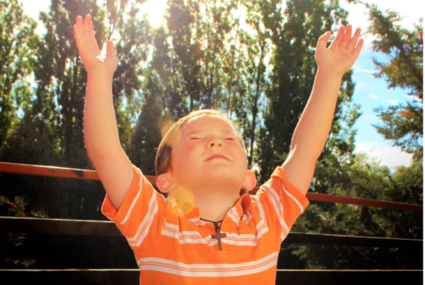a young boy with an orange polo and a wooden cross necklace lifts his arms in prayer