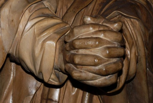 a wood sculpture of folded praying hands